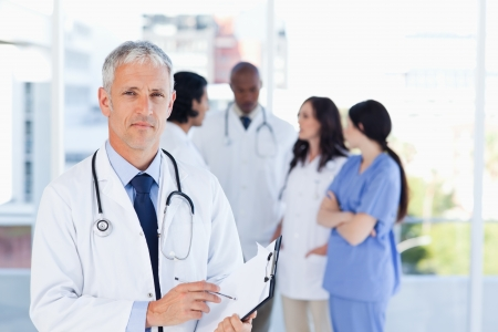 Mature doctor pointing seriously at something on his clipboard photo