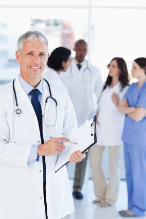 male doctor: Mature doctor smiling while pointing to a sentence on his clipboard