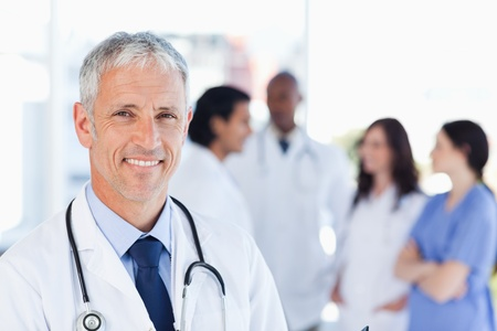 woman doctor: Smiling doctor waiting for his team while standing upright Stock Photo