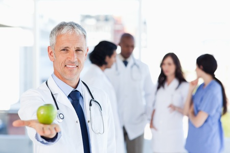 Smiling doctor holding a green apple in his right hand photo