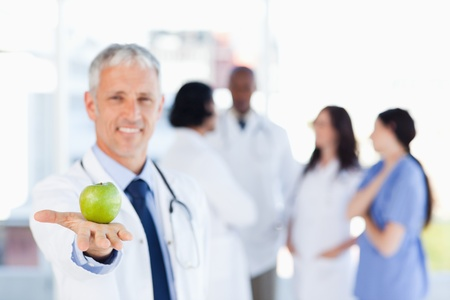 Smiling mature doctor holding an apple photo