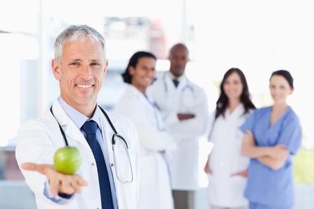 医者は彼のチームが彼を見ている間にリンゴを保持笑みを浮かべてください。 写真素材