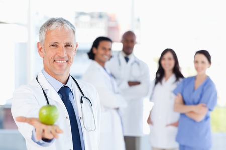 nutritionist: Smiling doctor holding an apple while his team is looking at him