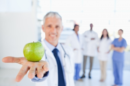 Green apple held by a doctor with a medical team behind him