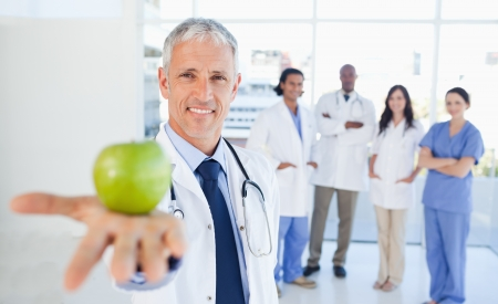 Medical interns in the background looking at their doctor who is holding an apple photo