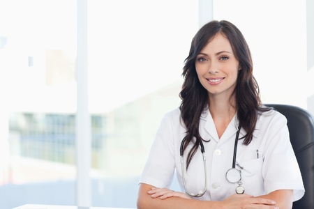 doctor's office: Young smiling doctor sitting at the desk on a black chair with her arms crossed Stock Photo