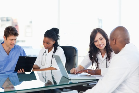 Smiling medical team working both on a laptop and a clipboard
