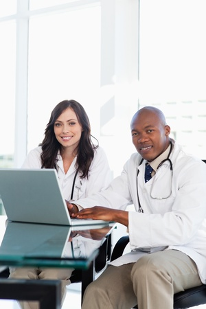 working hard: Smiling doctor working hard on a laptop while accompanied by his co-worker