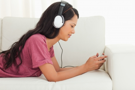 Young Latino frowning while listening to music on a sofa Stock Photo - 16185459