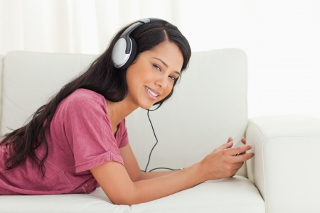Young Latino smiling while listening to music on a sofa with a smartphone Stock Photo - 16187287