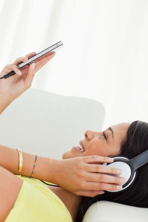 Close-up of a young Latino watching a video with earphones on her smartphone while lying on a sofa Stock Photo - 16184960