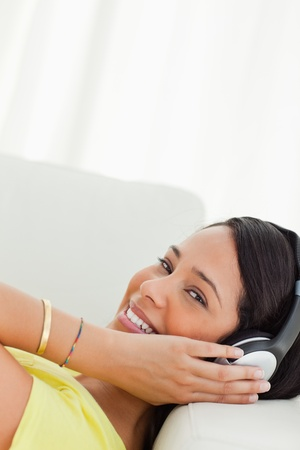Portrait of a young Latino with earphones while lying on a sofa Stock Photo - 16185105