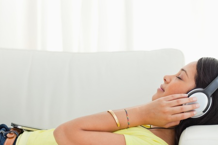 Young Latino listening music on a smartphone while lying on a sofa Stock Photo - 16184637