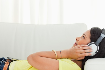 Young Latino listening music with a smartphone while lying on a sofa Stock Photo - 16184803