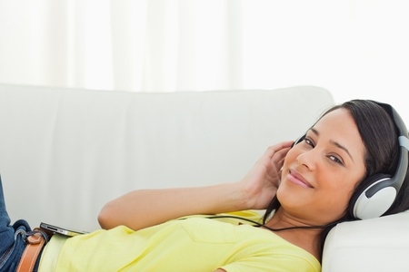 Portrait of a young Latino listening music on a smartphone while lying on a sofa Stock Photo - 16184962