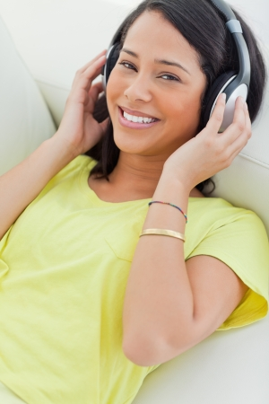 Portrait of a smiling Latino listening music on a smartphone while lying on a sofa Stock Photo - 16236285