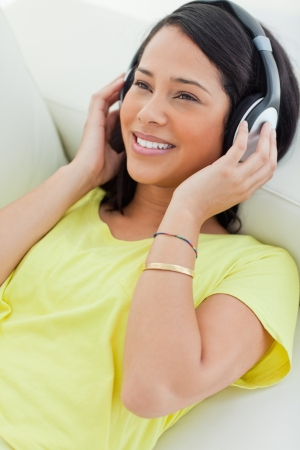 Close-up of a smiling Latino listening music on a smartphone while lying on a sofa Stock Photo - 16236268