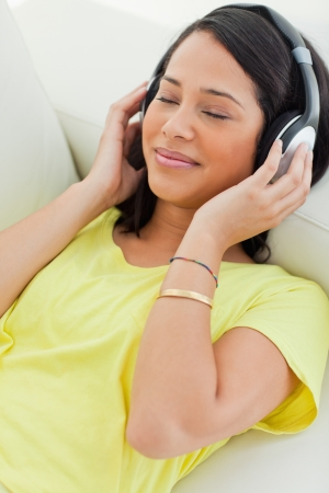 Close-up of a smiling Latino enjoying music on a smartphone while lying on a sofa Stock Photo - 16236359