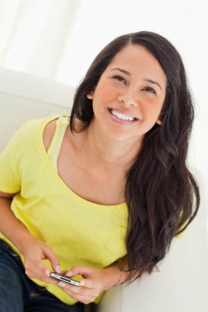 High-angle view of a happy Latino looking up while sitting on a sofa with her smartphone Stock Photo - 16235505