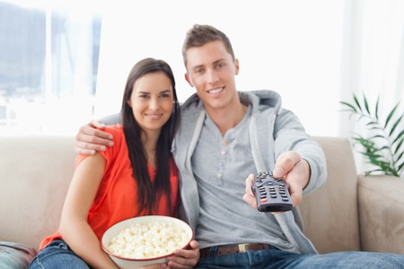 A focused shot on the tv remote on the mans hand as a couple embrace and smile photo