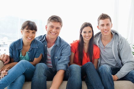 leaning forward: A smiling group leaning forward slightly as they look into the camera while sitting on the couch