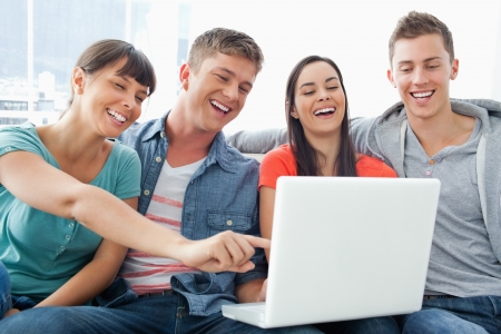 they are watching: A laughing group of friends around a laptop watching the screen as they sit with one girl pointing the screen
