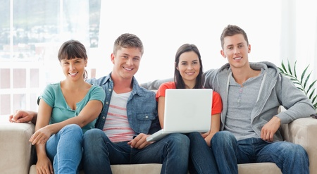 A smiling group sit on the couch as they look at the camera while they hold a laptop in front of them photo
