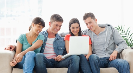 A group of friends sit together on the couch watching the laptop while smiling Stock Photo - 16235193