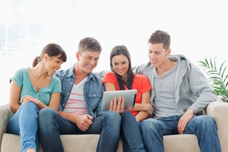 sit around: A smiling group sit around a tablet pc and watch the screen while on the couch