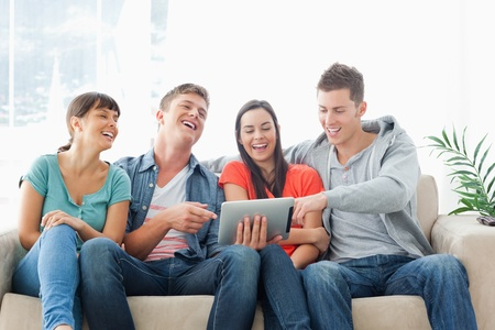 A group of friends watch the tablet pc and laugh as one man points to something on the screen Stock Photo - 16238065