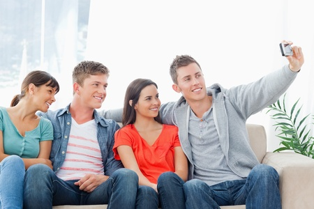 A smiling group of friends pose for a photo while sitting on the couch beside each other Stock Photo - 16238008