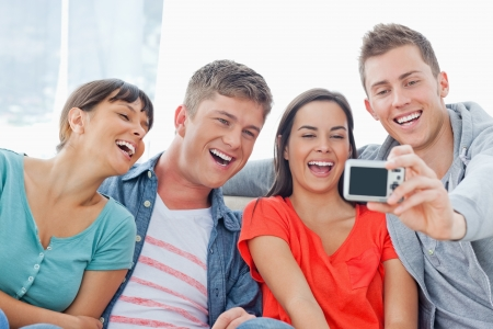 A laughing group of friends pose for a photo being taken in front of them Stock Photo - 16238185