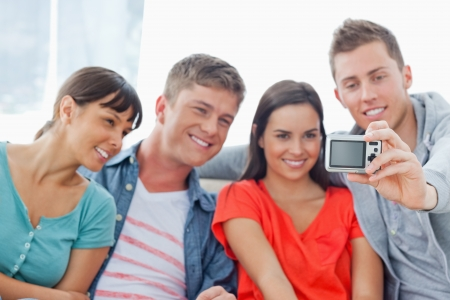 A smiling group pose for a photo together as they sit on the couch  Stock Photo - 16237265