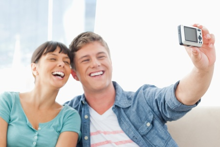 A couple pose together for a photo as they laugh while on the couch Stock Photo - 16234825