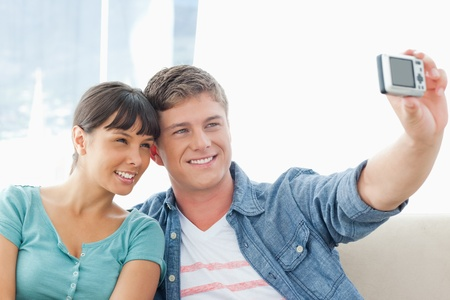 A smiling couple sit on the couch and pose together for a photo Stock Photo - 16237694