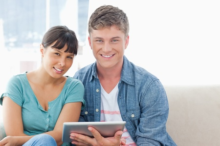 A couple on the couch with a tablet pc smiling as they look straight ahead into the camera Stock Photo - 16238101