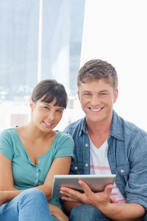 A close up shot of a couple holding a tablet pc while looking into the camera Stock Photo - 16238186