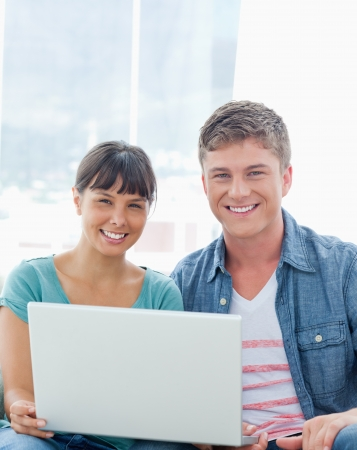 A couple with a laptop smiling as they look into the camera as they sit together photo