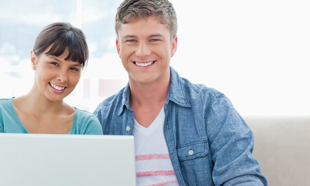 A smiling couple look into the camera as they hold a laptop in their hands Stock Photo - 16235506