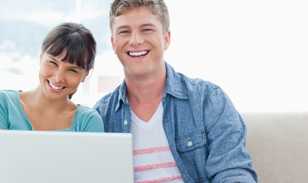 A couple looking into the camera as they smile while holding a laptop in their hands Stock Photo - 16235180