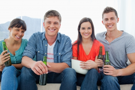 A group with beers in their hands as they sit on the couch together smiling Stock Photo - 16238233