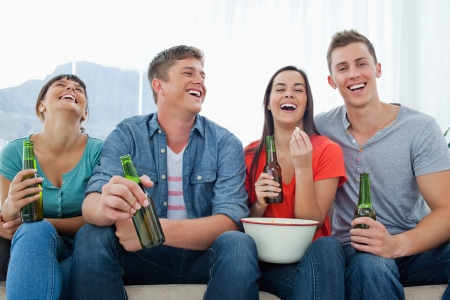 A laughing group of friends sitting with popcorn and beer as they have fun together Stock Photo - 16238224
