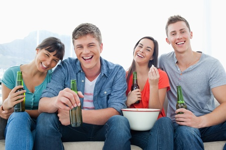 A laughing group of friends enjoying some beers and popcorn together photo