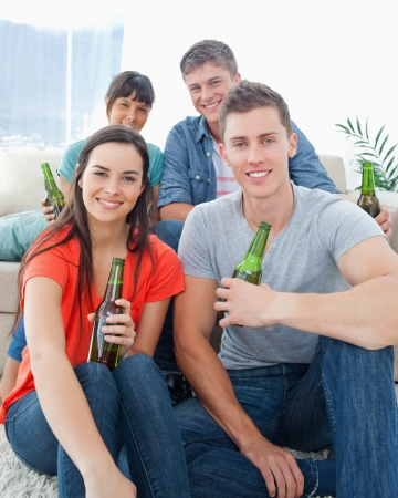 A smiling group of friends as one couple sit on the floor and the other couple sit on the couch with beers  Stock Photo - 16237689