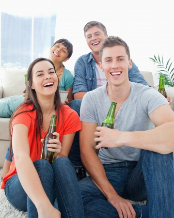 A group of friends sitting on the couch and the floor as they hold beers in their hands while laughing photo