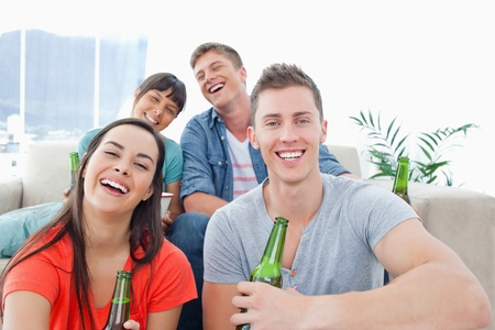 A laughing group inside the house enjoying beer and having fun together photo