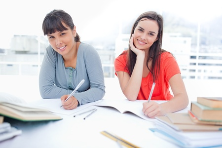 A girl and her friend both smile as they do homework together and look into the camera photo