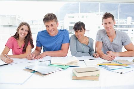 estudiantes universitarios: Cuatro estudiantes sonrientes miran hacia la c�mara en una biblioteca