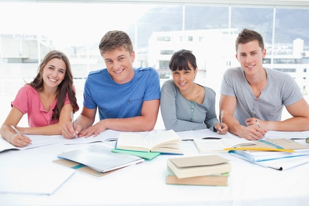 students studying: Four smiling students look up into the camera in a library