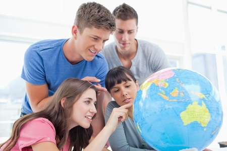 half globe: Four smiling students around a globe as two of them point to places in the world